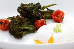 Poached eggs with roasted broccolette and cherry tomatoes