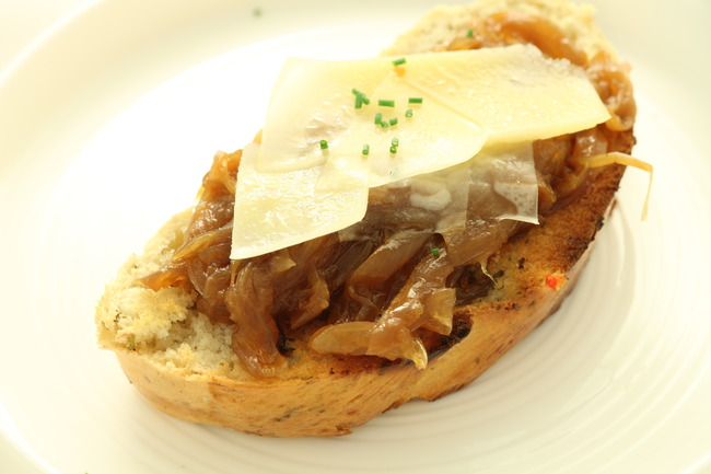 Onion confit crostini with gruyere shaving and chive